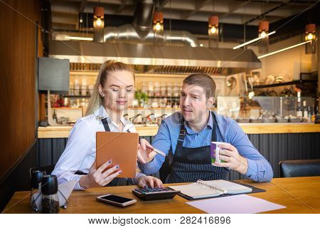 Young Man And Woman Going Through Paperwork Together In Their Restaurant. Small Family Restaurant Ow