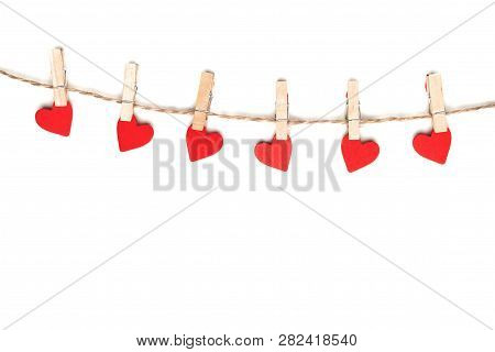 Clothes Pegs And Red Paper Hearts On Rope Isolated On White Background
