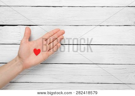 Heart In The Hand On A Wooden Background