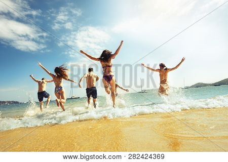 Big Group Of Friends Runs At Sea Beach. Tropical Vacations Concept