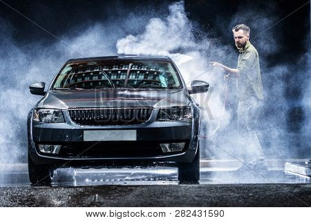 A Car Washer Washes A Gray Car With A High-pressure Washer At Night In A Car Wash. Expensive Adverti
