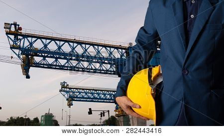 Engineer Or Worker Hold Yellow Helmet For Workers Security With Theodolite Transit Equipment At Cons