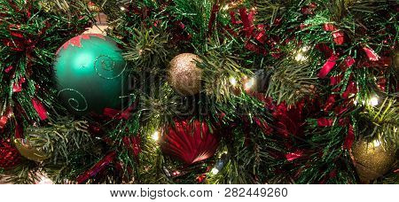 Festive Holiday Background. Christmas Tree Decorated With Ornaments And Illuminated With Multi Color