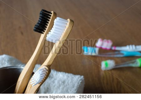 Three Bamboo Toothbrushes Against Three Plastic Toothbrushes On Wooden Background