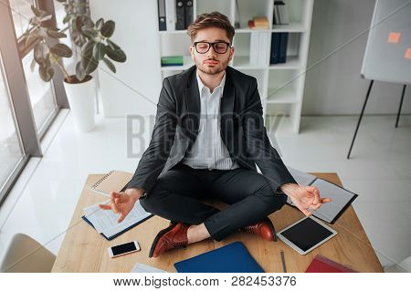 Calm Peaceful Young Man Meditating On Table In Meeting Room. He Sit With Legs Crossed Calm And Peace