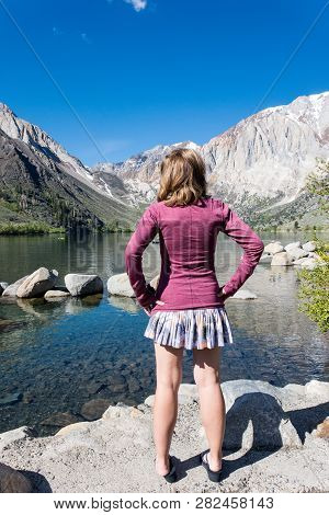 Female Adult Stands By Convict Lake In The Springtime, Located Off Of Us-395, Near Mammoth Lakes Cal