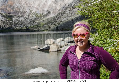 Blond Female Poses By Convict Lake In The Springtime, Located Off Of Us-395, Near Mammoth Lakes Cali