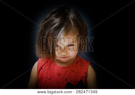 Tricky Child Look Up And Smiling Sly On Dark Background. Little Girl Devious