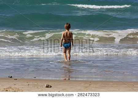 The Child Stands In The Sea In Front Of The Waves