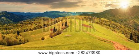 Panorama Of A Countryside In Mountains At Sunset In Evening Light. Path Down The Grassy Rural Hills