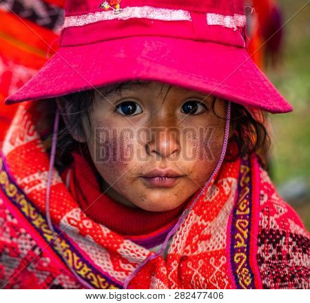 Peru, Cusco - 13 October 2018: Closeup of little girl in national bright red clothing with patterns and hat in Cusco