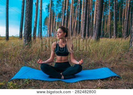 Beautiful And Young Girl Sitting On Rug In Lotus Position. Practicing Yoga In Asana Position. The Co