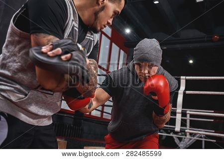 Close Quarter Boxing. Strong Tattooed Athlete In Sports Clothing Training On Boxing Paws With Partne