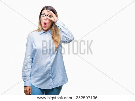 Young beautiful business woman wearing glasses over isolated background doing ok gesture shocked with surprised face, eye looking through fingers. Unbelieving expression.