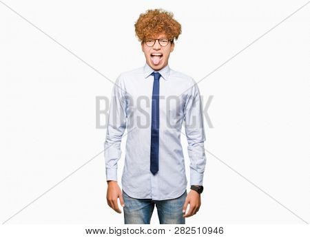 Young handsome business man with afro wearing glasses sticking tongue out happy with funny expression. Emotion concept.