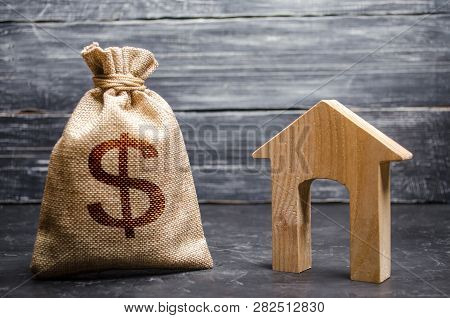 A Bag With Money And A House With A Large Doorway. Concept Of Real Estate Acquisition And Investment