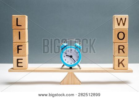 Blue Clock Between The Words Life And Work On The Scales. Choice Between Life And Work. The Concept