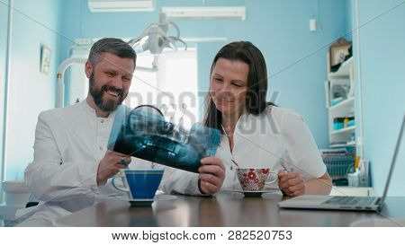Two Doctors Dentist Are Examining X-ray Photograph Using Loupe And Laptop