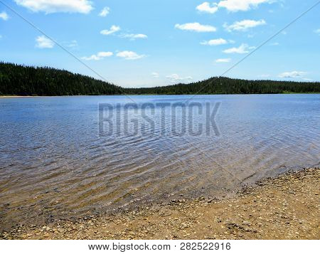 The pristine clear waters of Sandy Pond in Terra Nova National Park, Newfoundland and Labrador, Canada.  A nice remote location for a swim in clear fresh lake water surrounded by boreal forest. poster