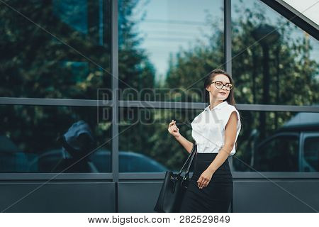Outoor Portrait Of A Beautiful Smiling Young Business Woman With Modern Building As Background