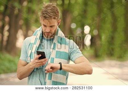 Man Athlete On Busy Face Setting Up Fitness Tracker, Nature Background. Sportsman Training With Pedo