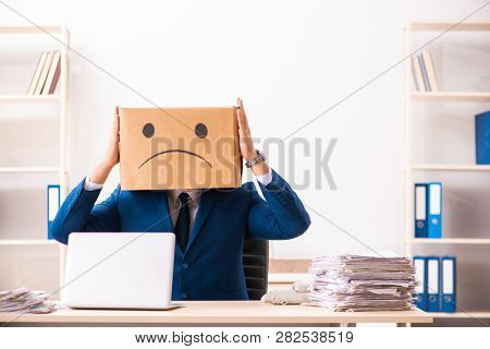 Unhappy man employee with box instead of his head