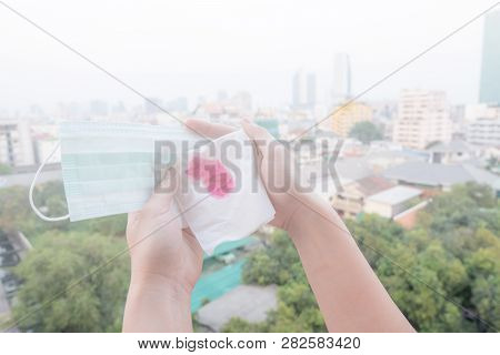 Woman Hands Or Female Hands Holding A Protective Mask And Napkin With Blood Because Of Air Pollution