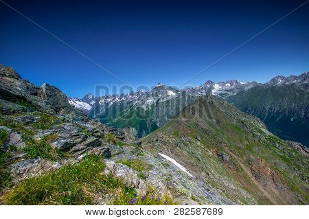 Mountain Summit Dombai-ulgen, Karachay-cherkessia, Russia. In The Background Are Glaciers And Peaks