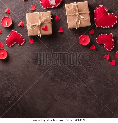 Happy Valentine's Day. Handmade Jewelry Red Hearts, Gifts In Craft Paper And Candles On Dark Backgro