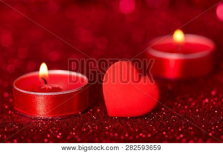 Romantic Valentine's Day. Lit Scented Candles And Red Heart On Bright Sparkling Background With Boke