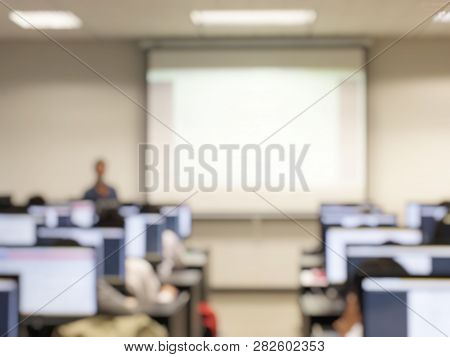 Blurred Image Of Group Of Students Are Learning And Lecture And Using Computer Together In Classroom