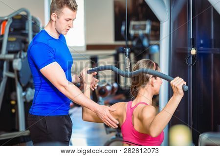Handsome and experienced personal trainer guiding a beautiful woman while exercising for pectoral muscles and shoulders at a modern fitness club