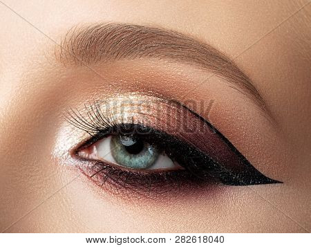 Close Up Of Beautiful Woman Eye With Multicolored Fashion Makeup And Modern Eyeliner Wing. Studio Sh