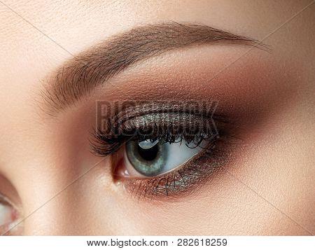 Close Up Of Beautiful Woman Eye With Multicolored Smokey Eyes Makeup. Studio Shot