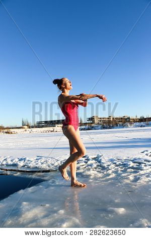 Young woman crosses herself plunging into icy water during Ukraine poster