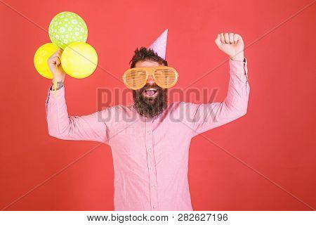 Hipster In Giant Sunglasses Celebrating Birthday. Man With Beard And Mustache On Happy Face Holds Bu