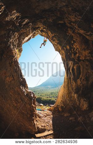 Rock Climber Climbs Into The Cave. Rock In The Form Of An Arch. The Woman Trains On A Natural Terrai
