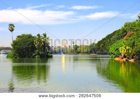 Lake in city park and biggest golden stupa in Shwedagon Zedi Daw (Great Dagon Pagoda, Golden Pagoda), Yangon, Myanmar (Burma). On blue sky background poster