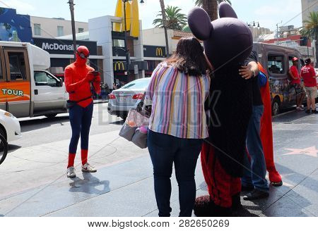 HOLLYWOOD, CALIFORNIA - SEPT 2, 2018: A person in a Spiderman costume takes a photo of tourists posing with other charactes in costume.