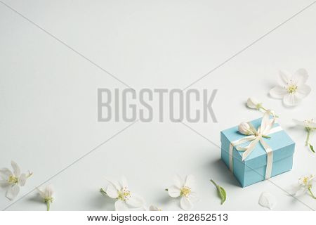 Pink Gift Surrounded By Apple Flowers. Gentle Background, Copy Space. Present For Mothers Day, Sprin