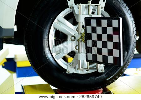 The Black And White Alignment Tool At The Metal Wheel Of White Car While Waiting On The Stop Positio