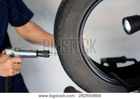The Blur Of Mechanic Holding A Drill And Drilled At  X Mark On Tire  During Repair The Leak Hole