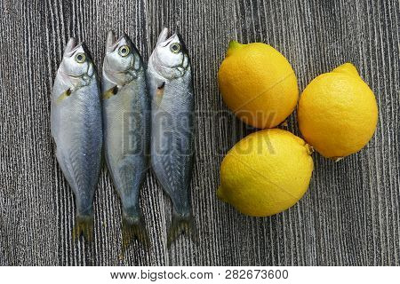 Small Bluefish And Lemon, On Wooden Background