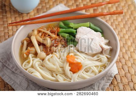Chicken and udon noodle soup with Shimeji mushrooms, carrot, onion, and asparagus beans