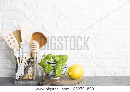 Kitchen Tools, Olive Cutting Boan A Kitchen Shelf Against A White Brick Wall. Fresh Basil And Lemon.