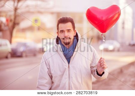 Urban Romance: Smiling Handsome Adult Man Standing In The City Street With Air Balloon Shaped As Red