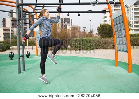 Ecstatic Fit Girl Warming Up On Playground, Jumping And Raising Knee. Young Woman Doing Cardio Inter