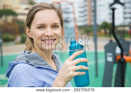 Happy Sporty Girl Standing On Playground And Holding Open Shaker. Young Woman In Sports Hoodie Drink
