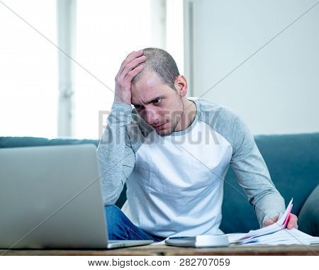 Upset Man In Stress Paying Credit Card Online Debts And Counting Finance With Laptop And Bank Papers