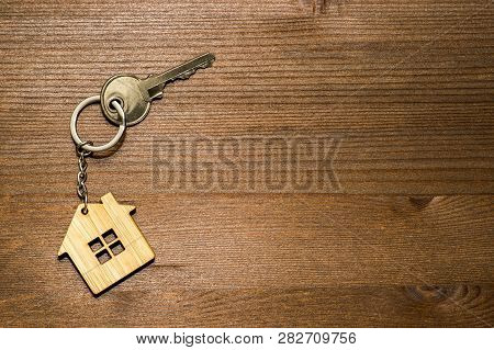 The Symbol Of The House In The Form Of A Keychain With A Metal Key On A Brown Vintage Wooden Backgro